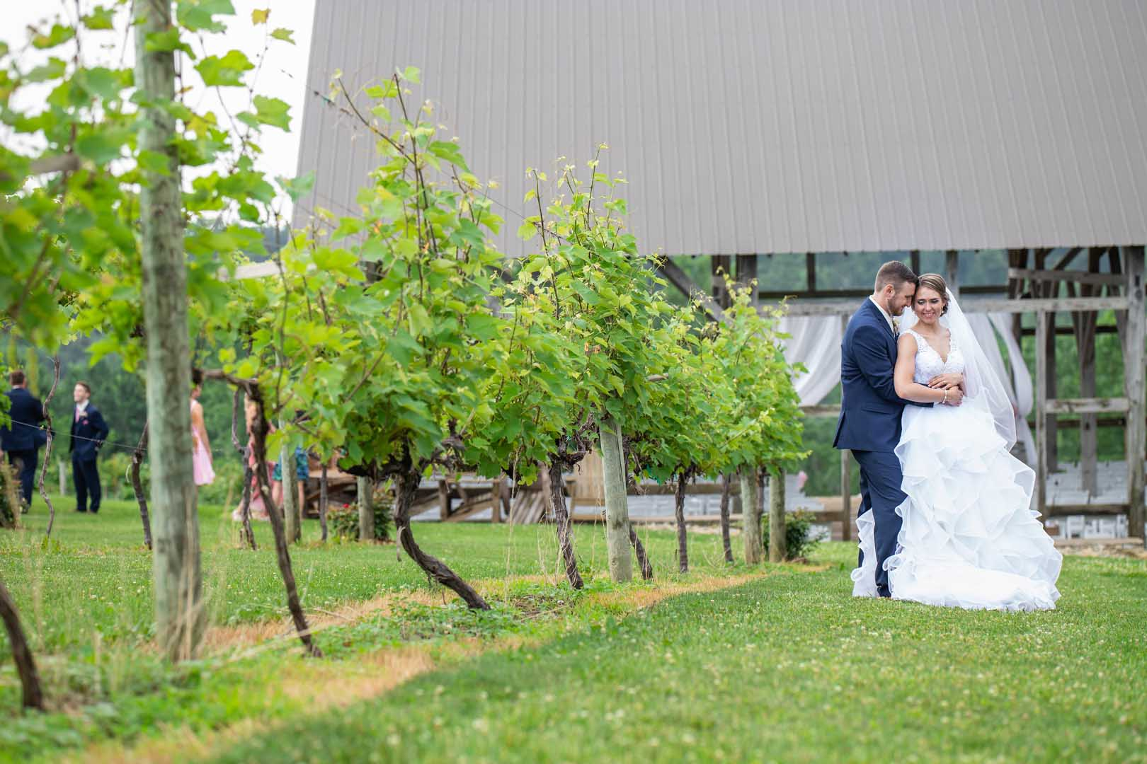 Bride and groom embracing before their wedding ceremony with a timber barn as a backdrop