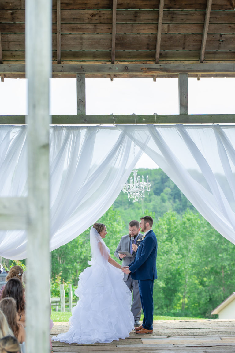 Bride and groom locking eyes during their wedding ceremony in a timber barn