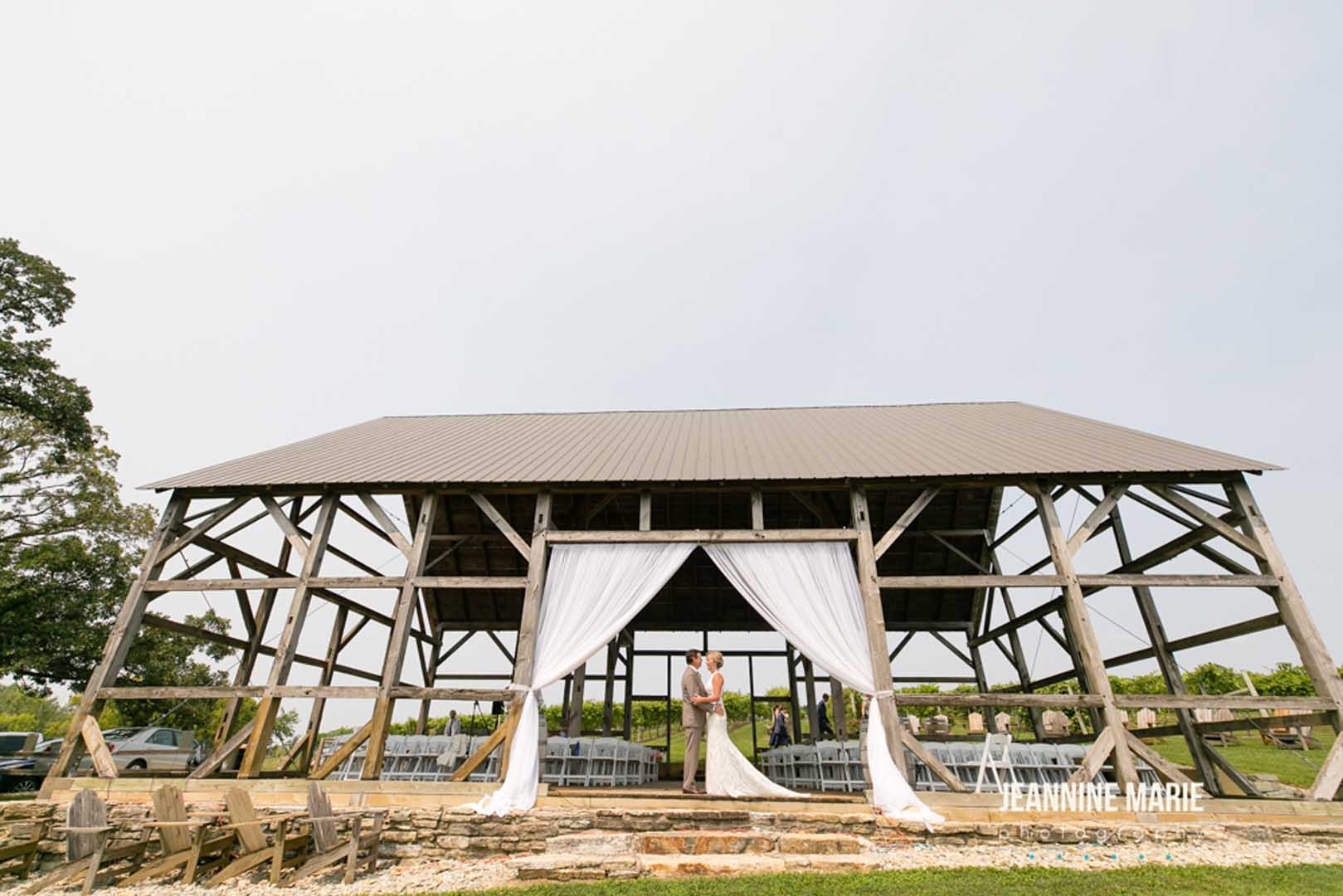 Couple posing before their wedding ceremony under the arch of a timber barn