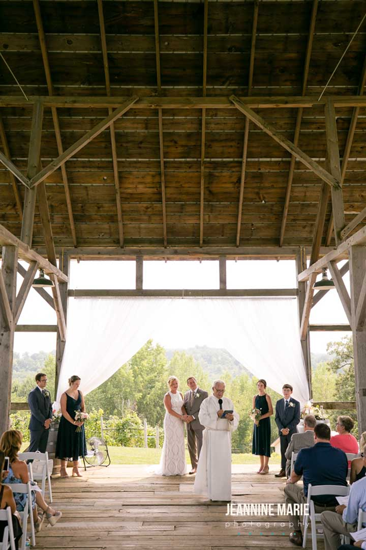 Priest marrying a couple at a timber barn wedding ceremony