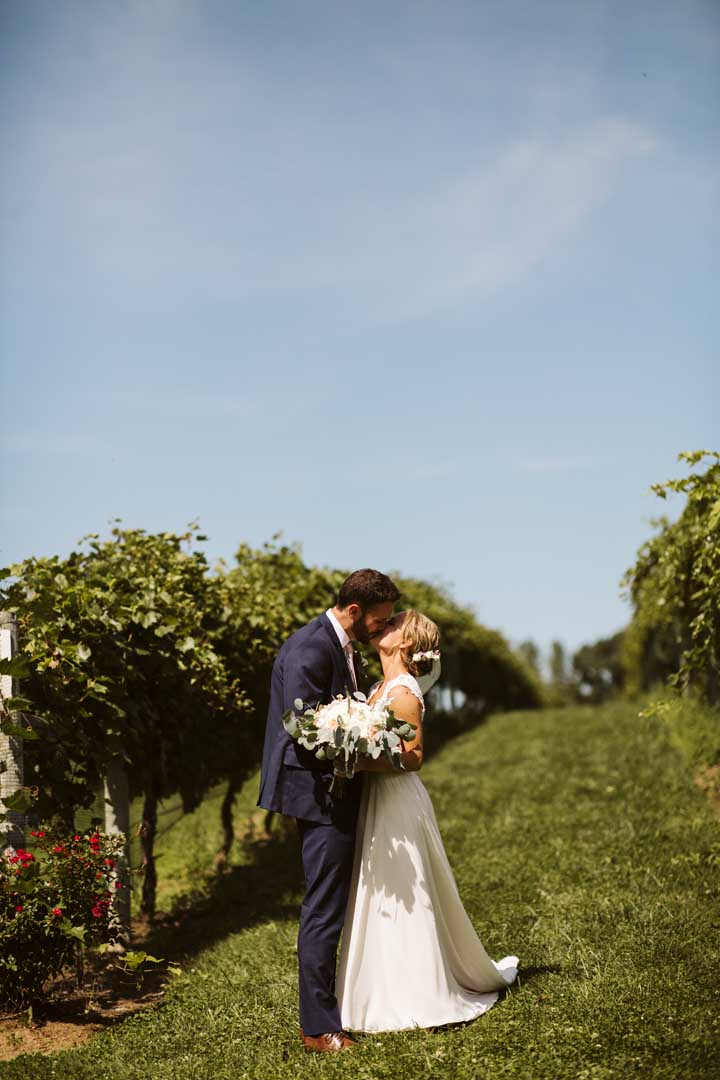 Bride and groom sharing a kiss next to grape vines at an outdoor vineyard wedding ceremony