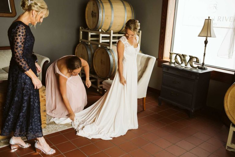 A bride with her mother and maid of honor adjusting her wedding dress before her ceremony