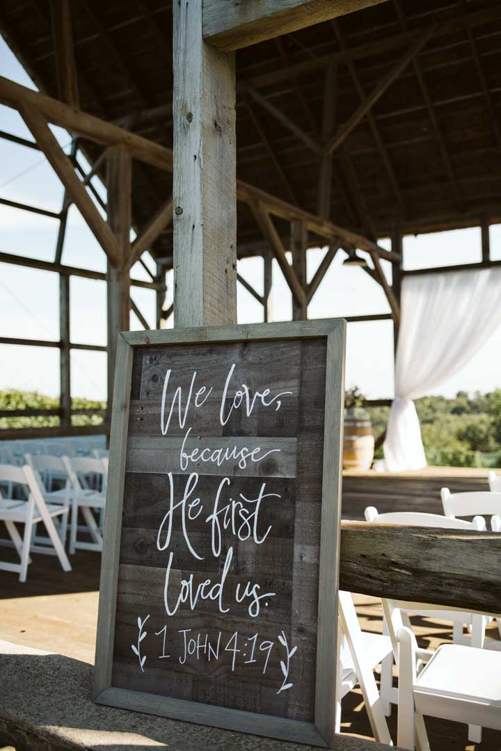 We love because he first loved us. Wooden sign at an outdoor wedding ceremmony