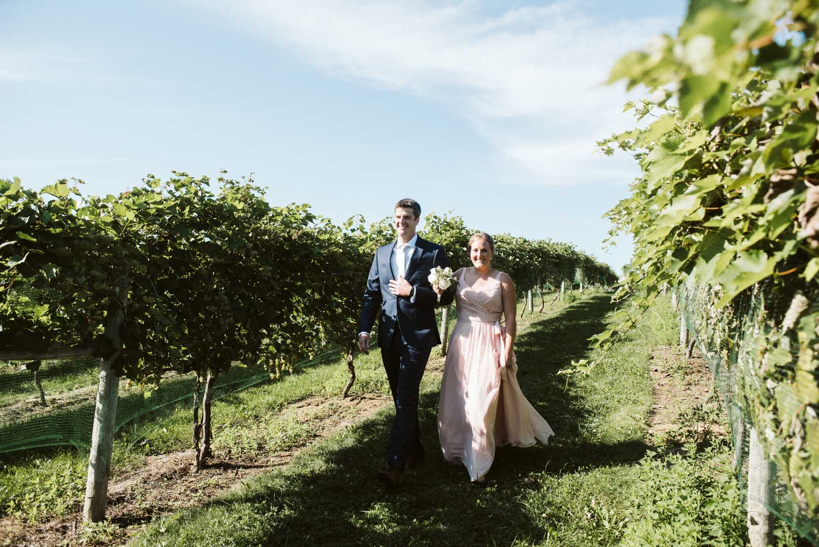 Two members of the bridal party walking through the vines to the ceremony site