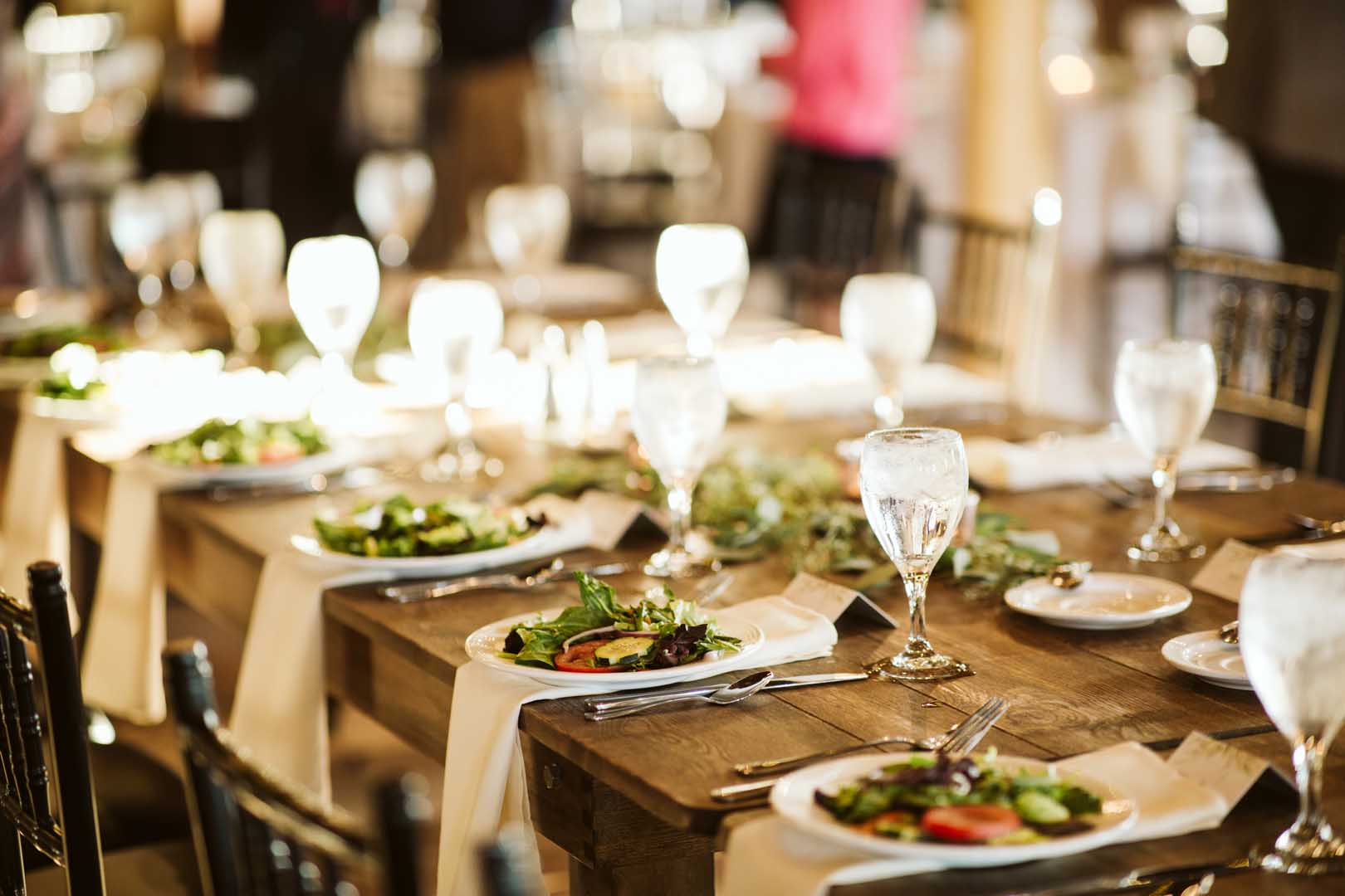 Head table for a wedding reception set with glasses and salads for the bridal party