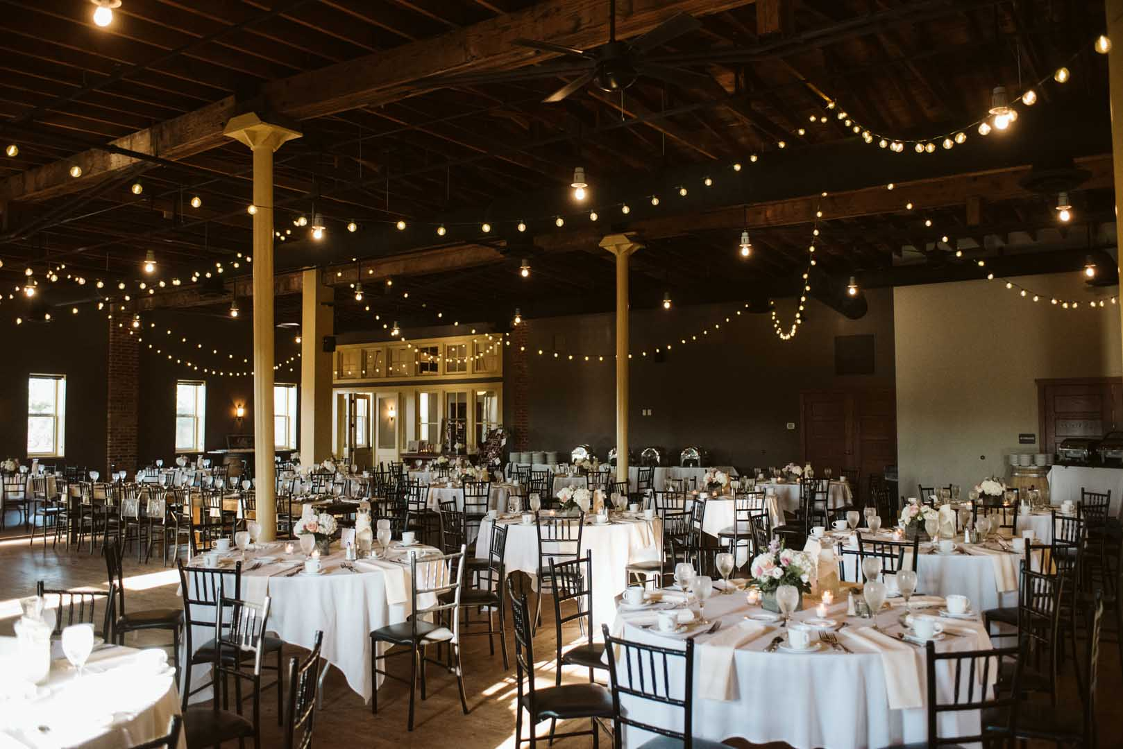 Event center at cannon river winery decorated with lights and white table cloths